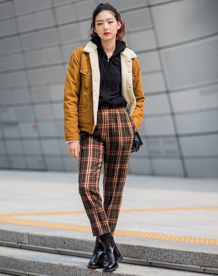 Девушка в брюках в клетку, черная толстовка и желтая утепленная куртка
