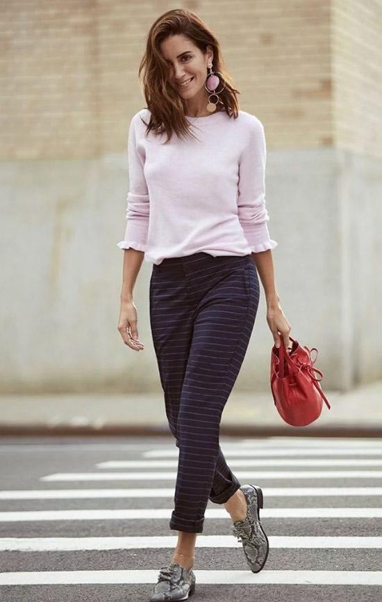 Девушка в брюках в клетку, розовая кофточка и лоферы со змеинным принтом
