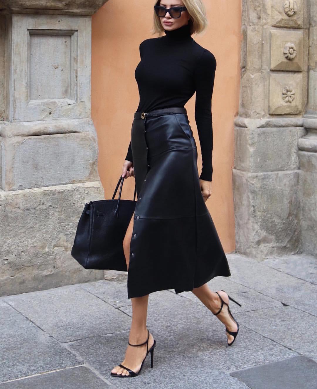Девушка в черной кожаной юбке миди, водолазка и черные ботильоны