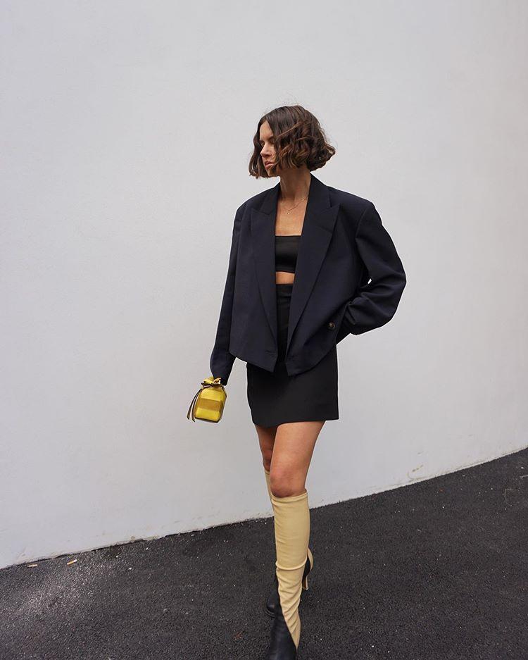 Девушка в черной мини юбке, блейзер и сапоги до колена