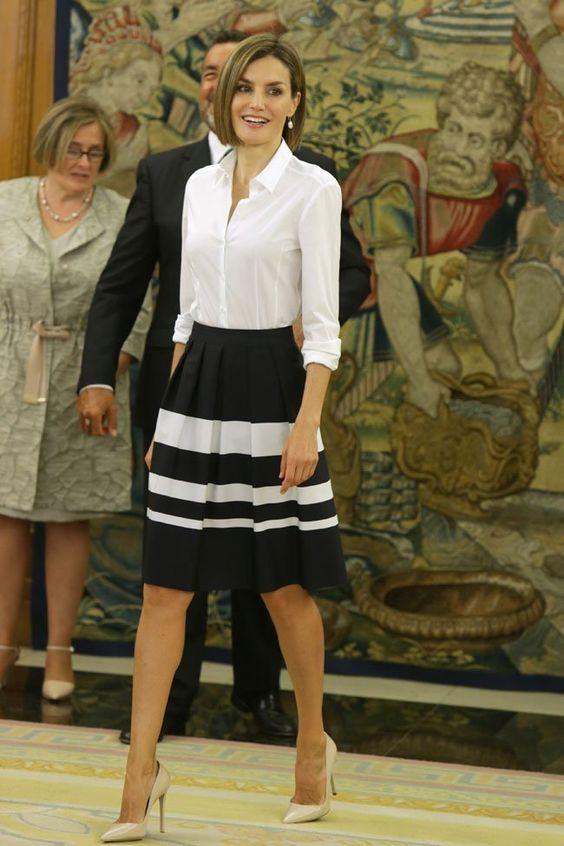 Девушка в черной юбке с белыми полосами и белой блузке, бежевые туфли