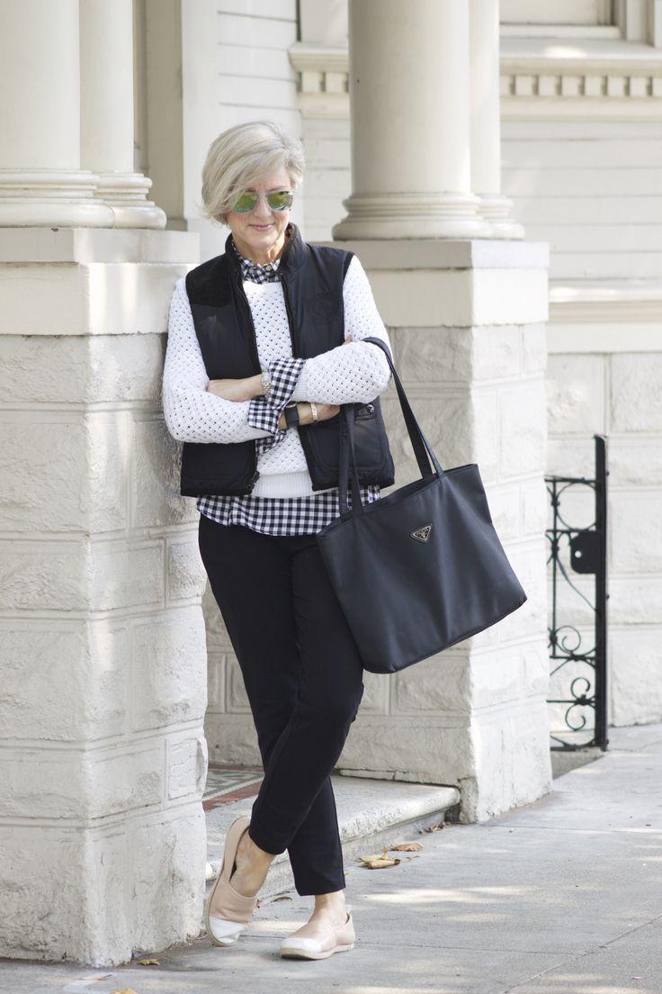 Девушка в черных брюках, белый свитер и жилет