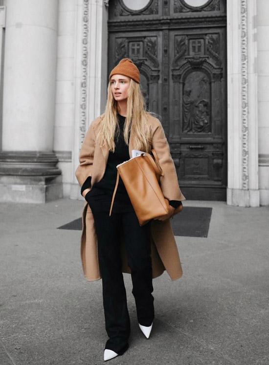 Девушка в черных брюках, бежевое классическое пальто и белые ботильоны