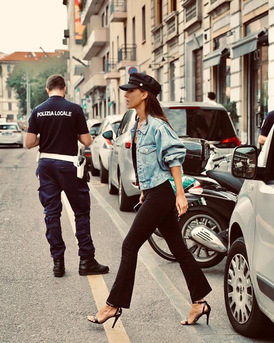 Девушка в черных брюках клеш, джинсовка и черные сандалии и кепи