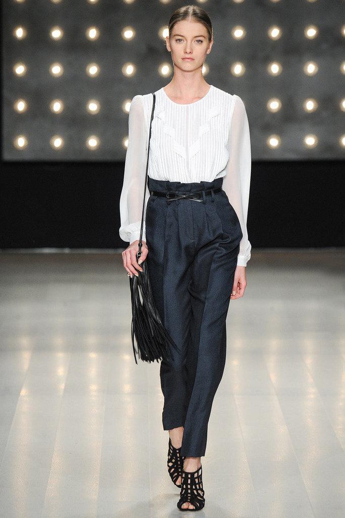 Девушка в черных брюках с завышенной талией, белая блузка и черные босоножки