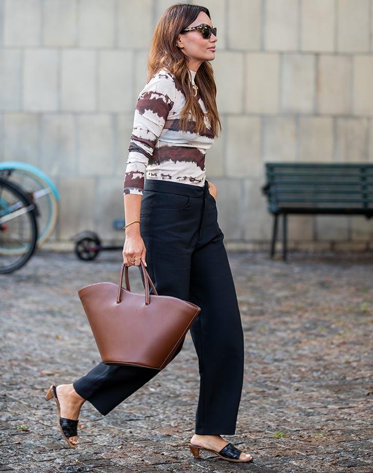 Девушка в черных брюках, водолазка, коричневая сумка