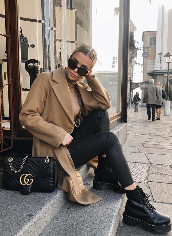 Девушка в черных леггинсах, бежевое пальто и черные ботинки
