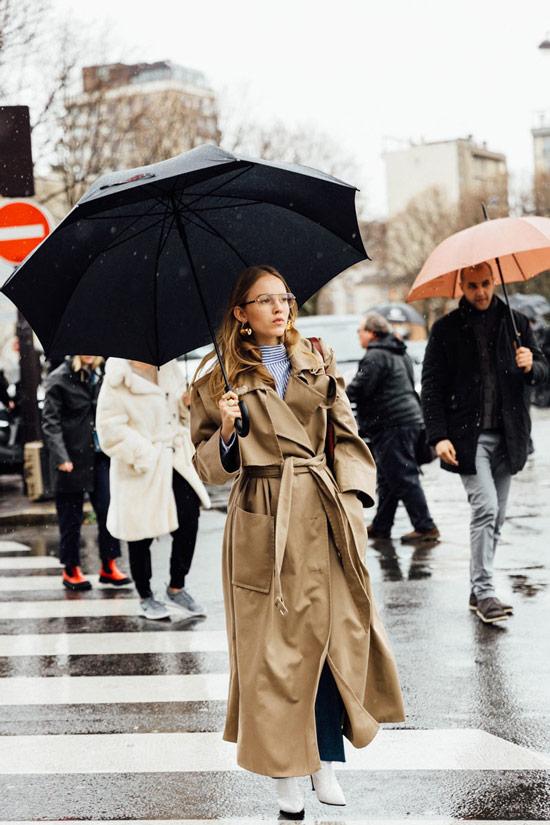 Девушка в длинном классическом плаще, джинсы, белые сапоги и зонт