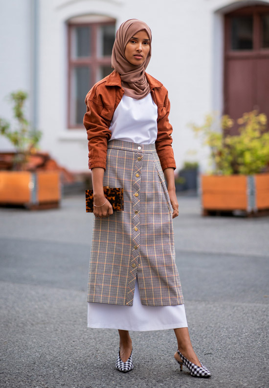 Девушка в клетчатой юбке миди, оранжевый бомбер и туфли на низком каблуке