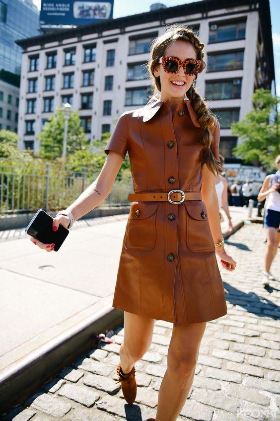 Девушка в коричневом кожаном платье с ремнем и ботильонах