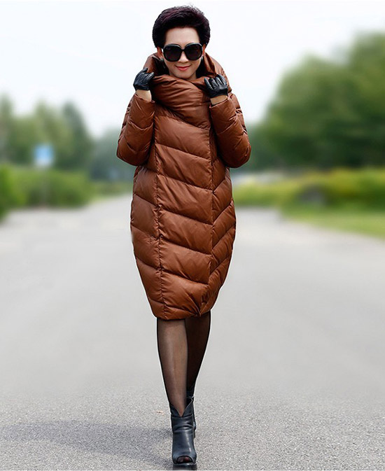 Девушка в коричневом пуховике по колено и черных ботильонах
