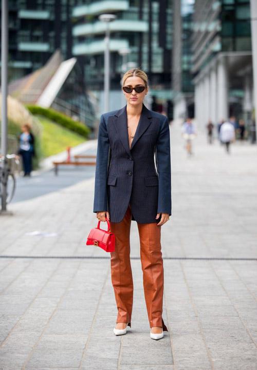 Девушка в коричневых кожаных брюках, синем блейзере и бежевых лодочках