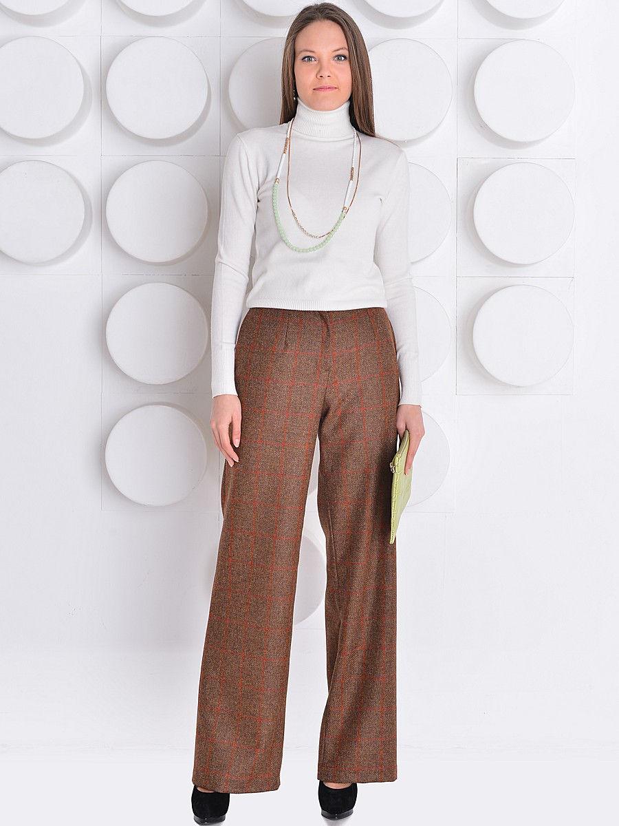 Девушка в коричневых широких брюках и белой водолазке