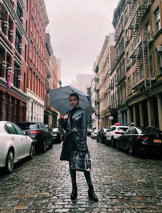 Девушка в кожаном плаще с поясом, черные ботинки и зонт