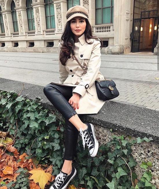 Девушка в кожаных штанах, бежевый плащ, кеды и черная сумочка