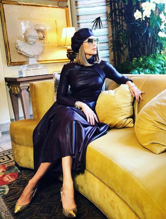 Девушка в кожаной черной юбке, кожаная водолазка и золотые туфли