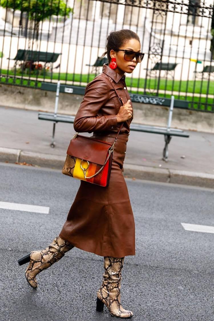 Девушка в кожаной юбке миди, коричневая рубашка и сапоги из змеиной кожи