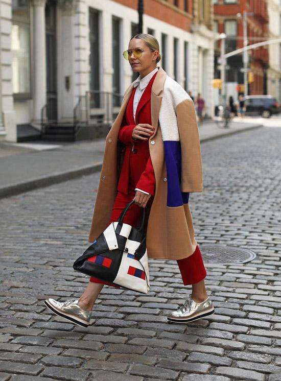 Девушка в красном костюме с укороченными брюками, бежевое пальто и серебристые кеды