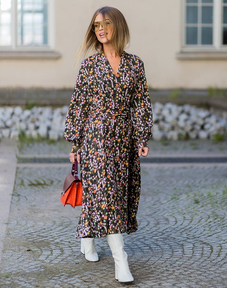 Девушка в легком цветочном платье, белые сапоги и оранжевая сумка