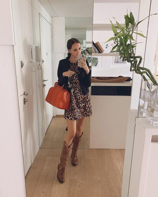 Девушка в мини платье с леопардовым принтом, ковбойские сапоги и черная куртка