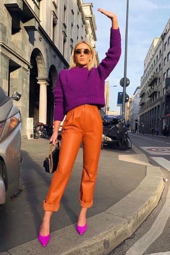 Девушка в оранжевых кожаных брюках, фиолетовый свитер и туфли на шпильке