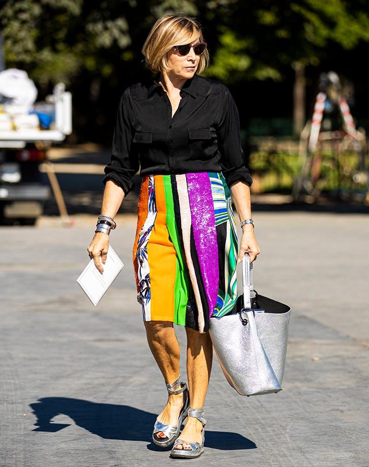 Девушка в разноцветной юбке карандаш, черная рубашка и серебристые сандалии