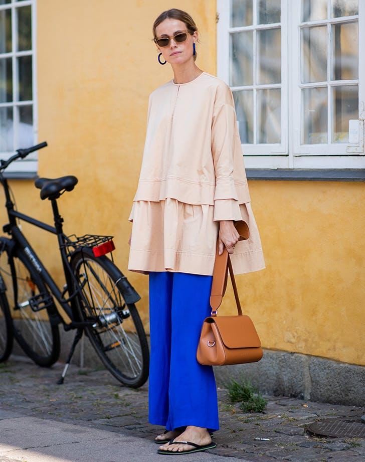 Девушка в розовой тунике, свободные синие брюки и сланцы