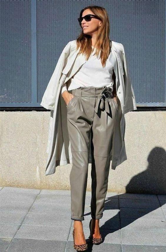 Девушка в серых кожаных брюках, белая водолазка и плащ