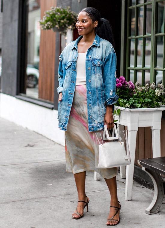 Девушка в шелковой юбке миди, джинсовая куртка оверсайз и черные босоножки на ремешках