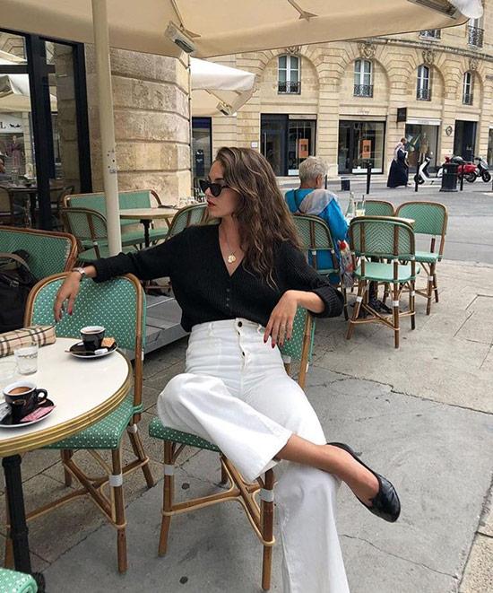 Девушка в широких белых брюках с завышенной талией и черная блузка