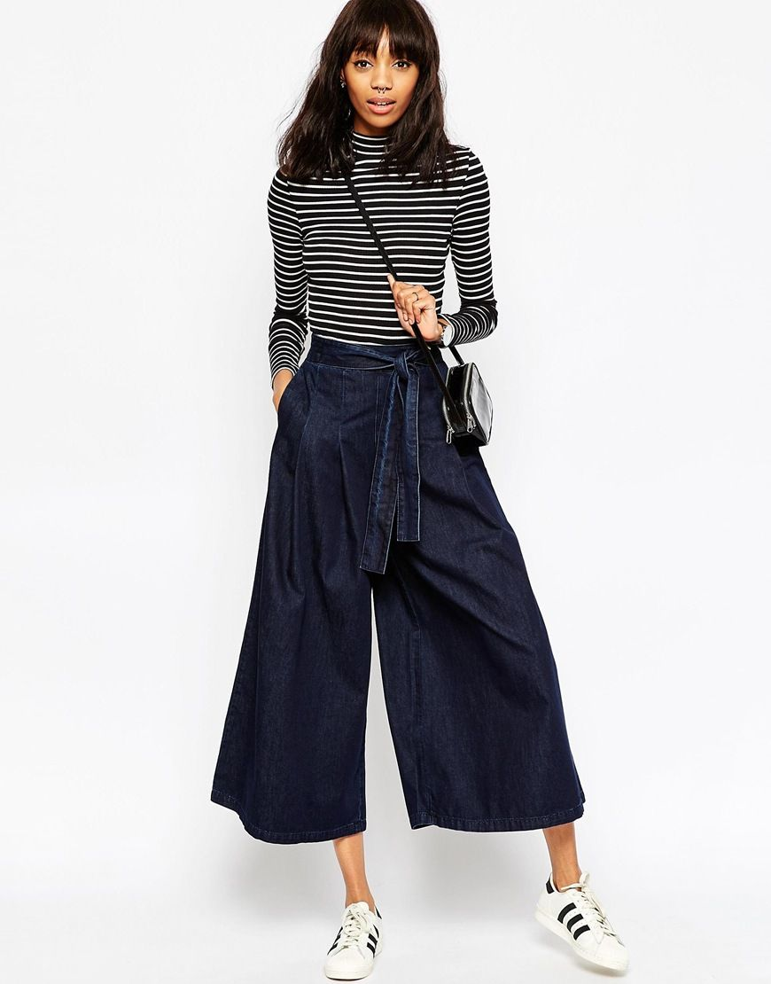 Девушка в широких джинсах с поясом и черно-белой водолазке в полоску