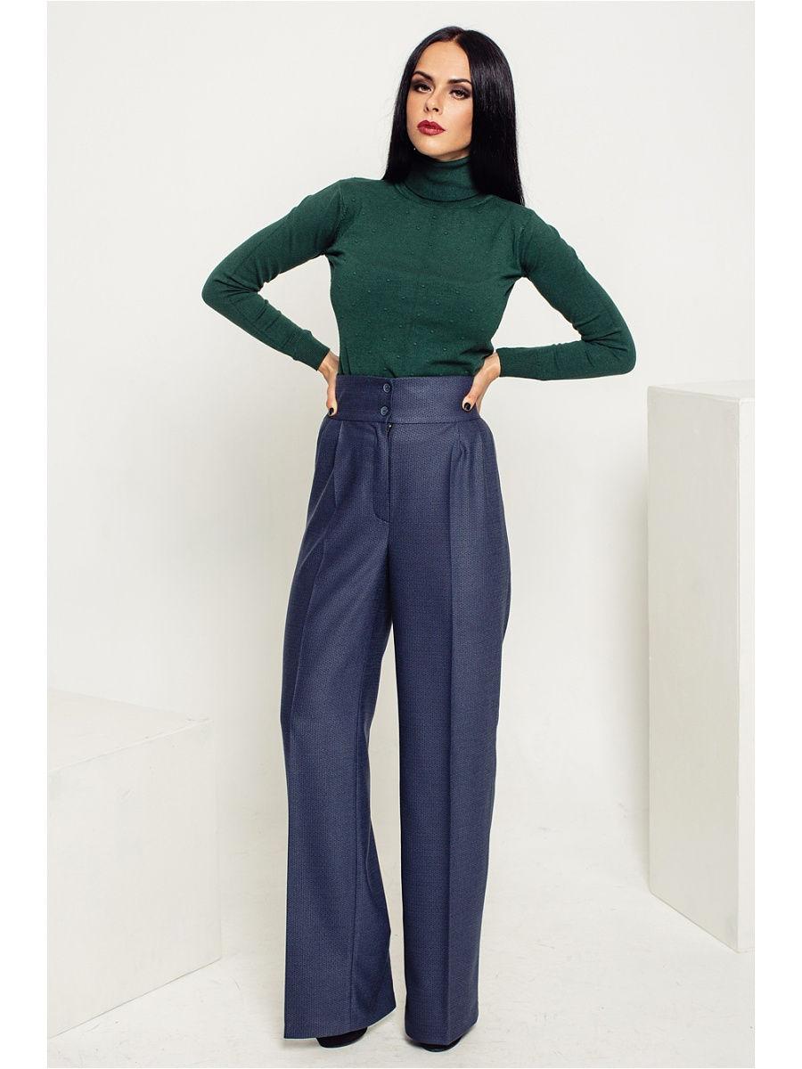 Девушка в синих широких брюках со стрелками и зеленая водолазка