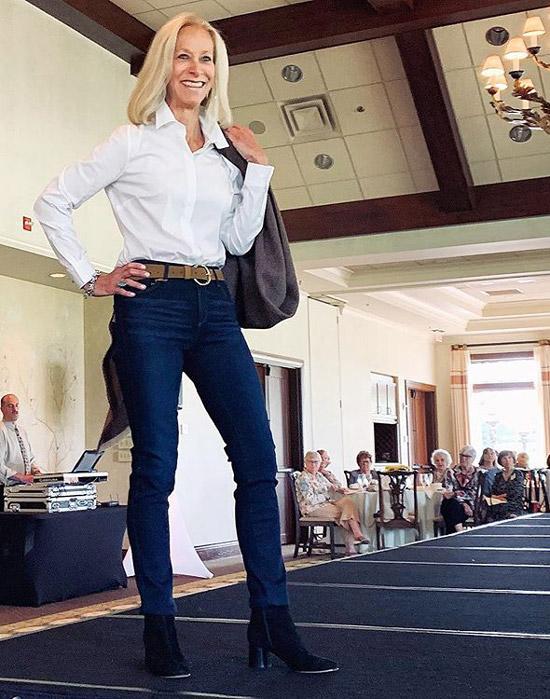 Девушка в темно синих джинсах, белая рубаша и черные ботильоны