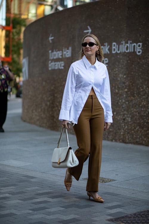 Девушка в туфлях с пряжкой, брюках и белой блузе