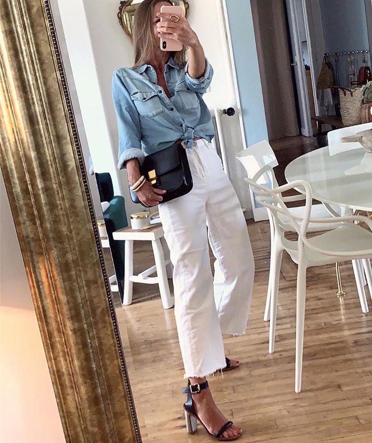 Девушка в укороченных белых джинсах, черные босоножки и голубая рубашка