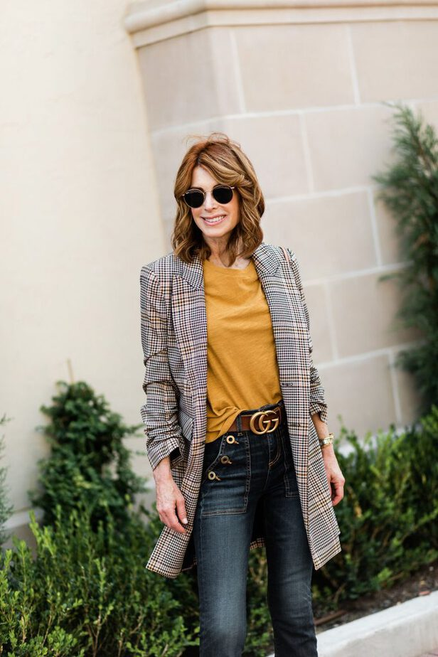 Девушка в узких джинсах, желтая футболка и удлиненный блейзер в клетку