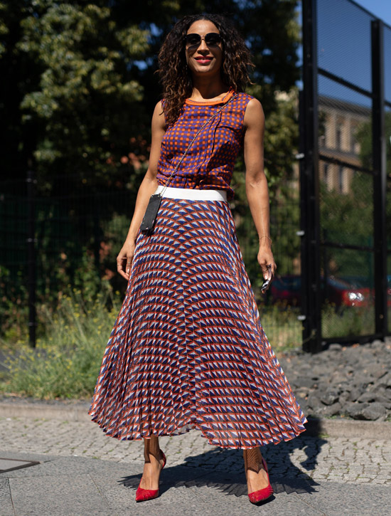 Девушка в яркой юбке, топ и красные туфли