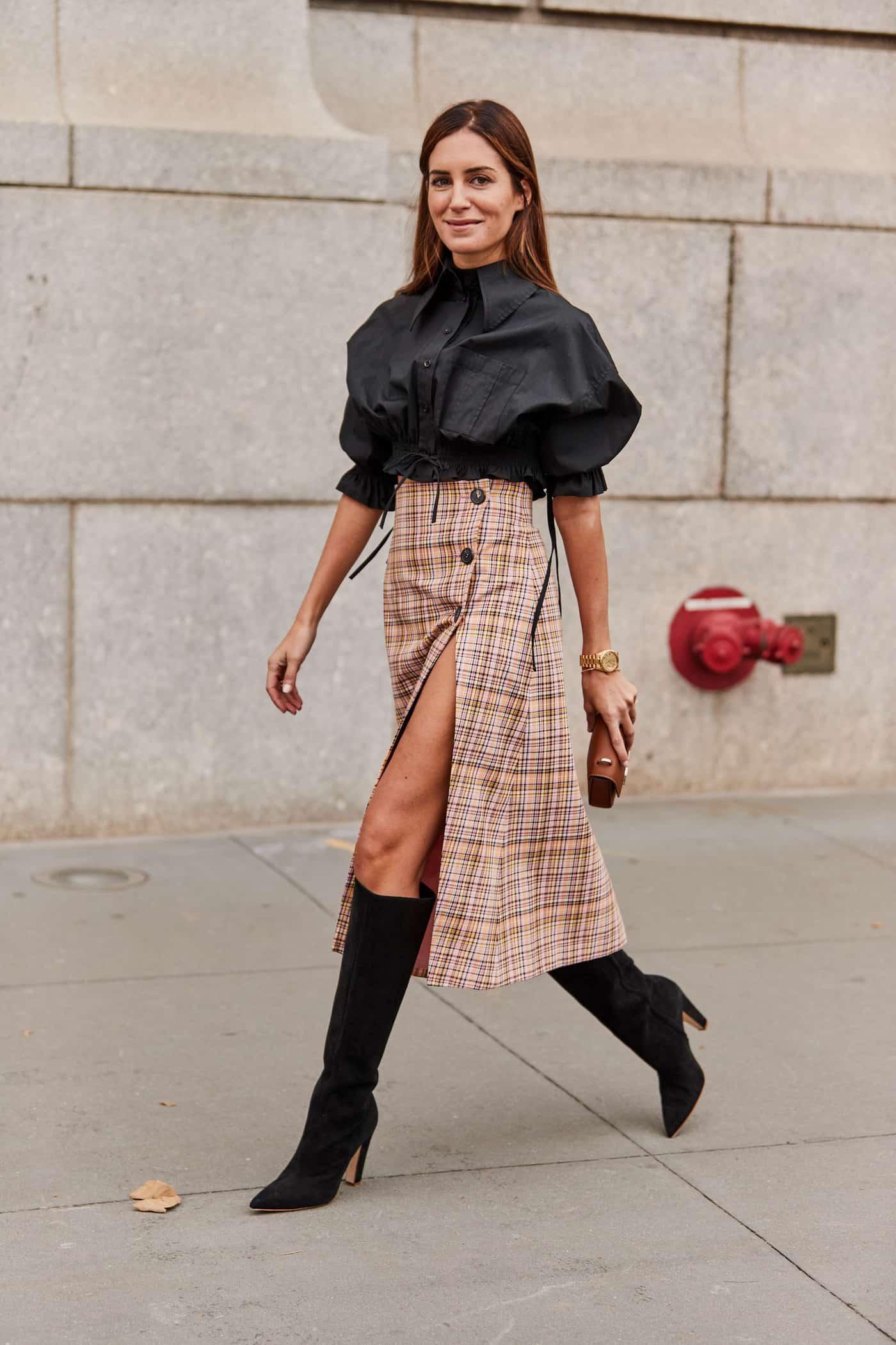 Девушка в юбке миди в клетку с разрезом и пышная блуза, черные сапоги на каблуке