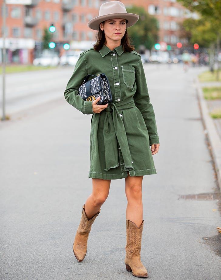 Девушка в зеленом платье рубашка, ковбойские сапоги и шляпа
