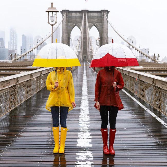 Девушки в ярких желтых и красных резиновых сапогах, дождивиках и зонты