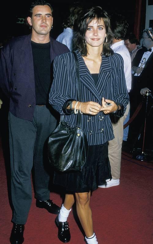 Кортни Кокс в черном платье по колено и блейзер в полосу с объемными плечами