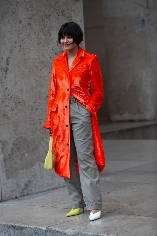 Maria Bernad в серых брюках, оранжевый лакированный плащ и туфли разного цвета