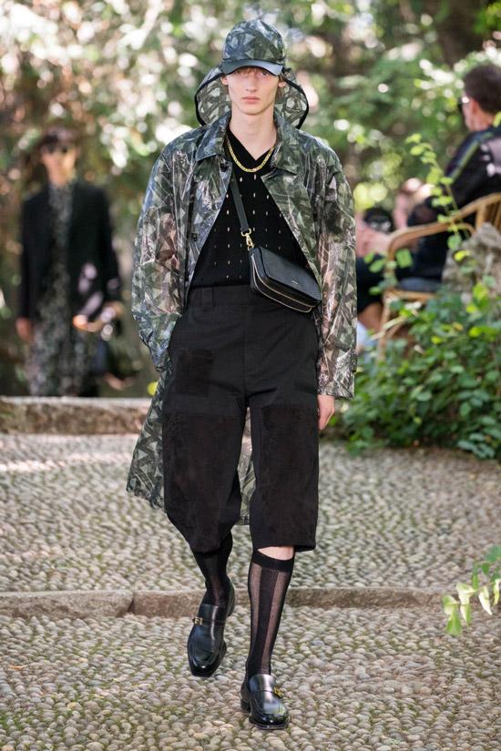 Модель в черных бриджах, плащ и черные туфли