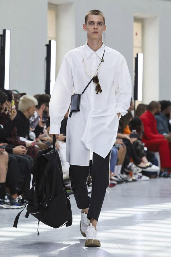 Модель в черных узких брюках, белые кеды и рубашка оверсайз