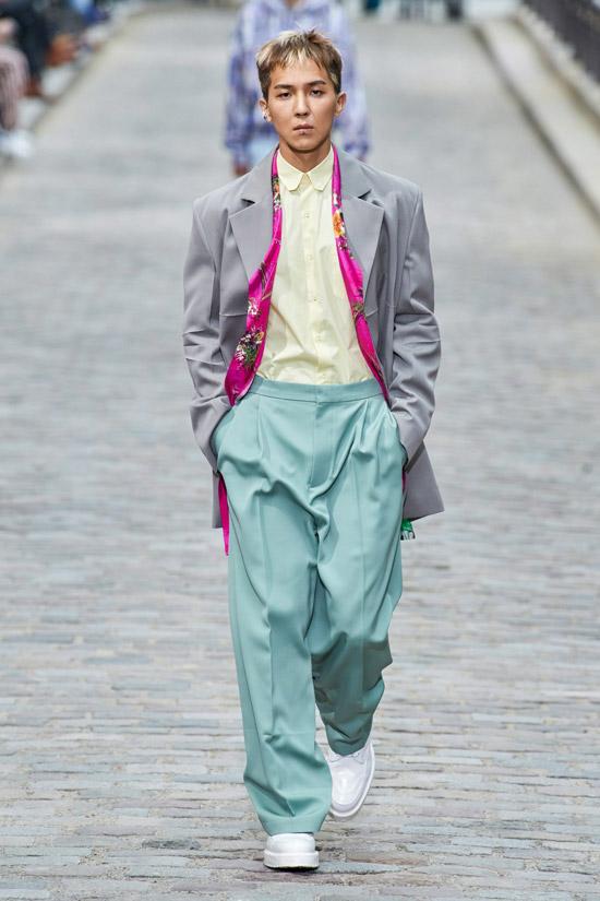 Модель в голубых широких брюках, рубашка и серый пиджак