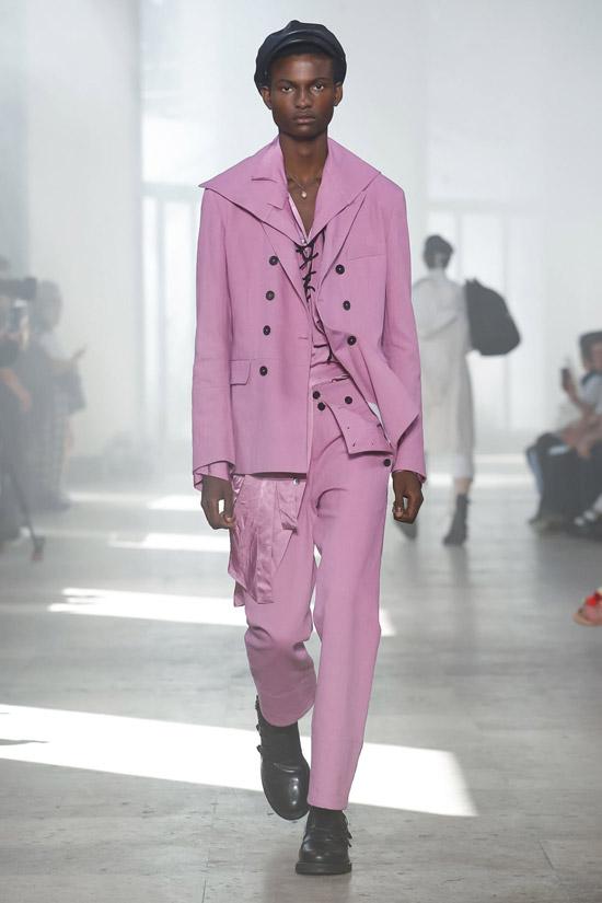 Модель в розовом костюме, черная кепка и ботинки