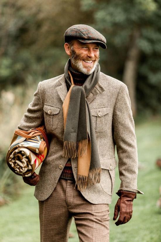 Мужчина в коричневых брюках в клетку, утепленный пиджак и кепка