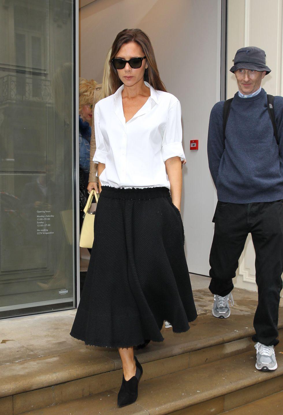 Виктория Бекхем в черной юбке миди и белой блузке