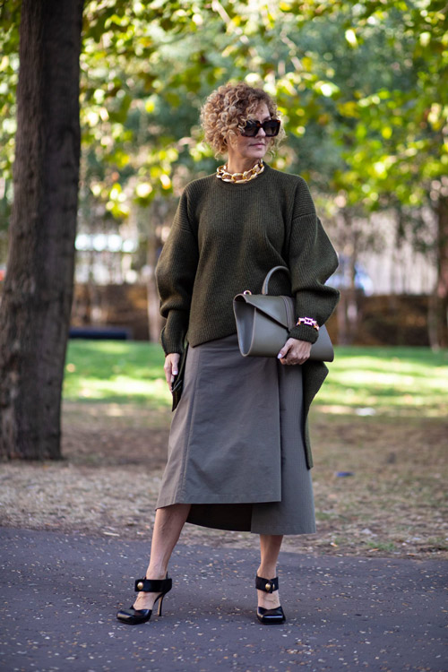 Женщина в серой юбке зеленом топе и черных туфлях