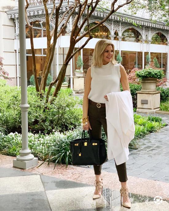 Блогер в белом топе, темных джинсах и светлом кардигане